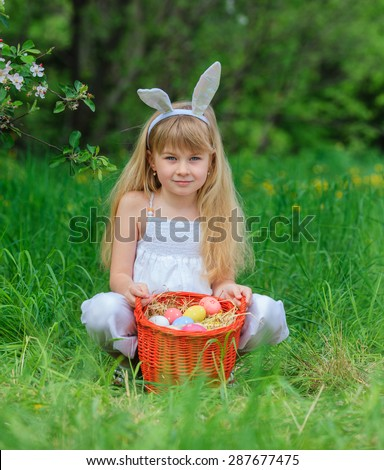 Adorable little girl wearing bunny ears playing with Easter eggs in blossoming dandelion on spring day - stock photo