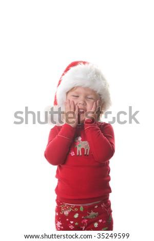 Adorable little girl wearing Christmas pajamas and a Santa hat - stock photo