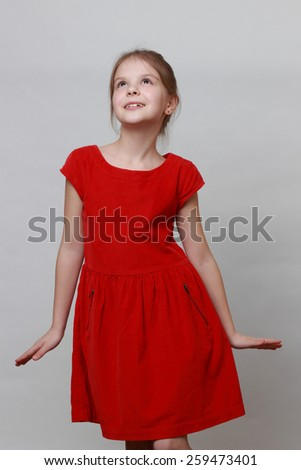 Adorable little girl wearing fashion red dress and dancing - stock photo
