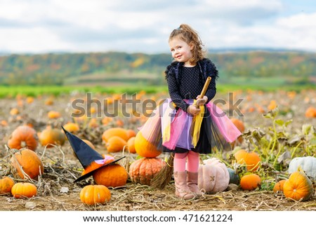 Adorable little girl wearing halloween witch costume having fun on a pumpkin patch. Traditional family festival with children.