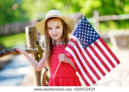Adorable little girl wearing hat holding american flag outdoors on beautiful summer day. Independence Day concept.