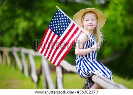 Adorable little girl wearing hat holding american flag outdoors on beautiful summer day. Independence Day concept. - stock photo