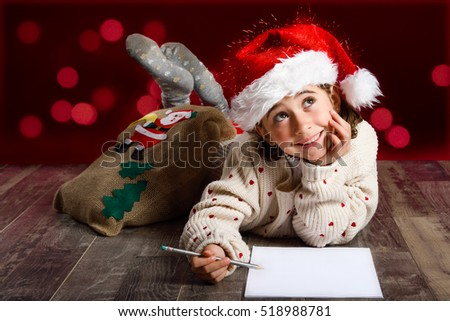 Adorable little girl wearing santa hat writing Santa letter on wooden floor. Winter clothes for Christmas. Red bokeh at the background