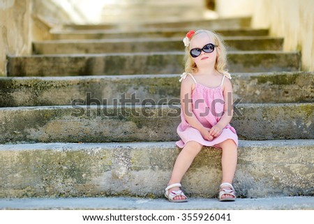 Adorable little girl wearing sunglasses sitting on stairs on warm and sunny summer day in typical italian town - stock photo