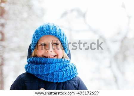 Adorable little girl wearing warm clothes outdoors on beautiful winter snowy day