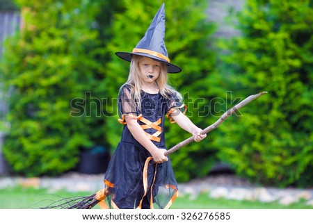 Adorable little girl wearing witch costume on Halloween at autumn day. Trick or treat. - stock photo