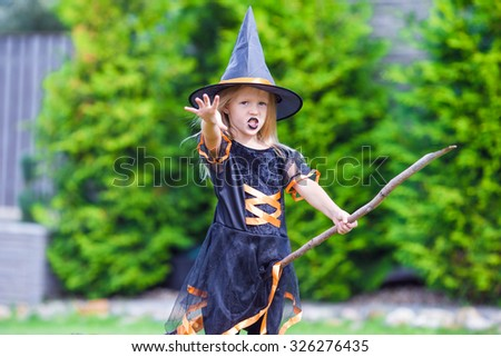 Adorable little girl wearing witch costume on Halloween outdoors. Trick or treat. - stock photo
