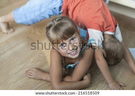 Adorable little girl while playing with her little brother - stock photo
