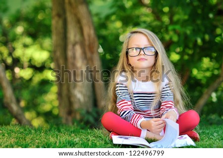 Adorable little girl with a book in the park - stock photo