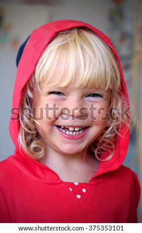 Adorable little girl with a funny face wearing red hoodie - stock photo