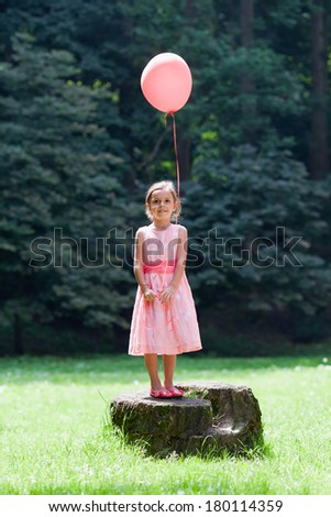 Adorable little girl with a red balloon on stump in park - stock photo
