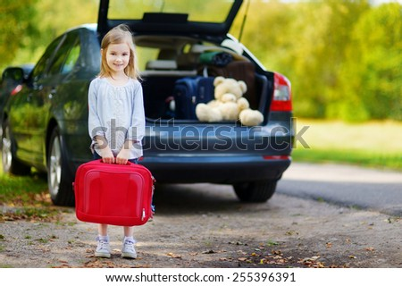 Adorable little girl with a suitcase leaving for a car vacation with her parents - stock photo