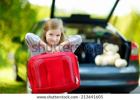 Adorable little girl with a suitcase leaving for a car vacation with their parents - stock photo