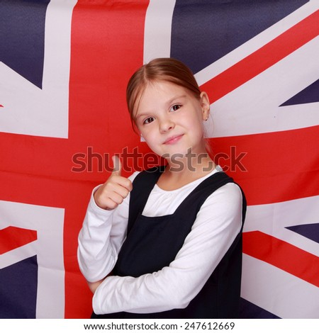 Adorable little girl with a sweet smile in school uniform - stock photo