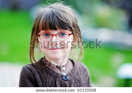Adorable little girl with beauty blue eyes in glases - stock photo