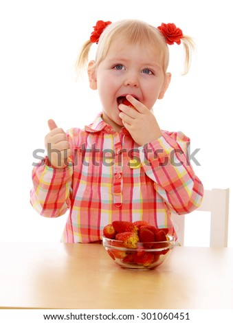 Adorable little girl with blond bunches in which braided roses. Girl sits at a table and eating from a large glass cup juicy strawberries. Hand girl showing a sign all is well-Isolated on white - stock photo
