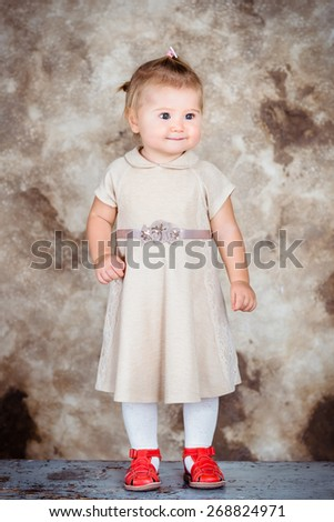 Adorable little girl with blond hair and plump cheeks wearing stylish beige dress and red shoes - stock photo