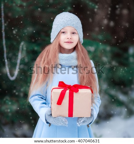 Adorable little girl with christmas box gift in winter outdoors on Xmas eve - stock photo
