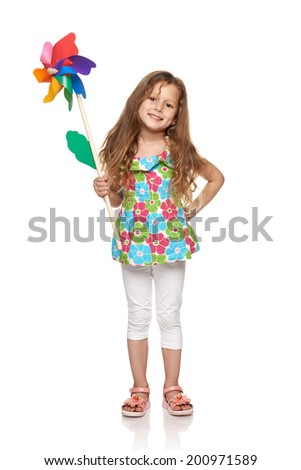 Adorable little girl with colorful windmill standing in full length over white background - stock photo