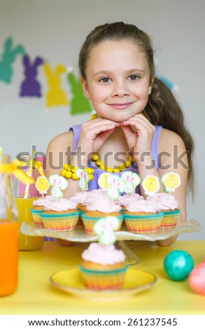 Adorable little girl with cupcakes in Easter scene