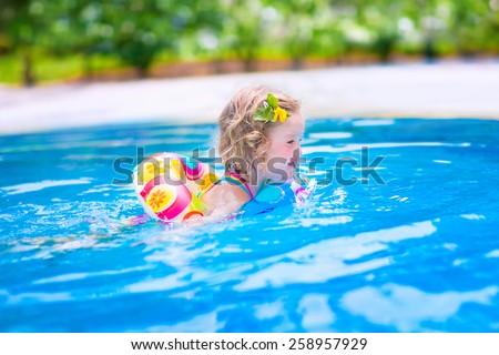 Adorable little girl with curly hair wearing a colorful swimming suit playing with water splashes at beautiful pool in a tropical resort having fun during family summer vacation - stock photo