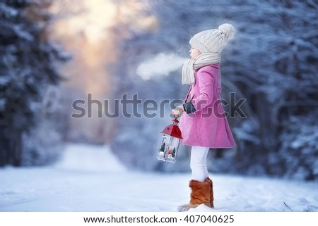 Adorable little girl with flashlight in frozen winter on Christmas outdoors - stock photo