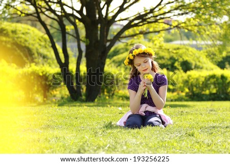 Adorable little girl with floral head wreath at the spring park, moscow, russia - stock photo