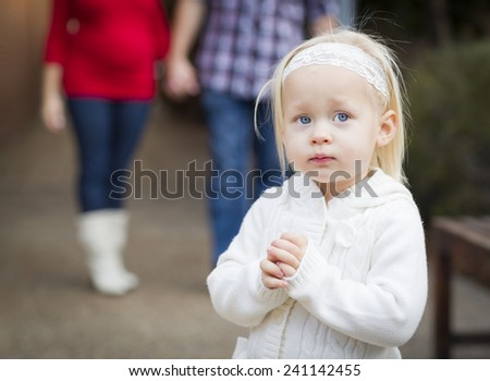 Adorable Little Girl with Her Mommy and Daddy Portrait Outside. - stock photo