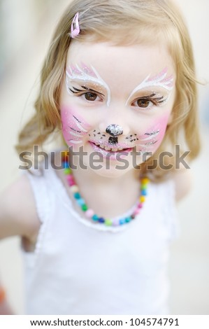 Adorable little girl with kitty painted face - stock photo