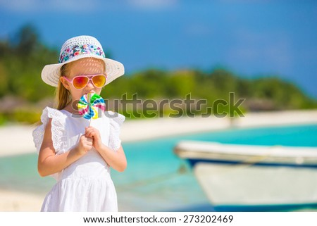 Adorable little girl with lollipop on tropical beach - stock photo
