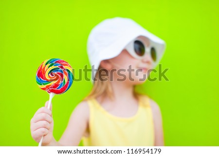 Adorable little girl with lollipop over colorful wall. Focus on candy - stock photo