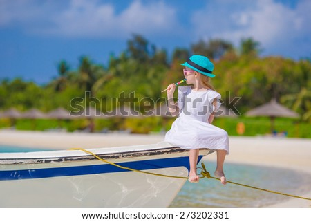 Adorable little girl with lollipop sitting on boat - stock photo