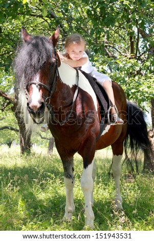 Adorable little girl with long hair and a sweet smile riding her pony - stock photo