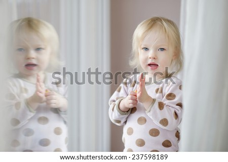 Adorable little girl with milk mustache standing by the window - stock photo