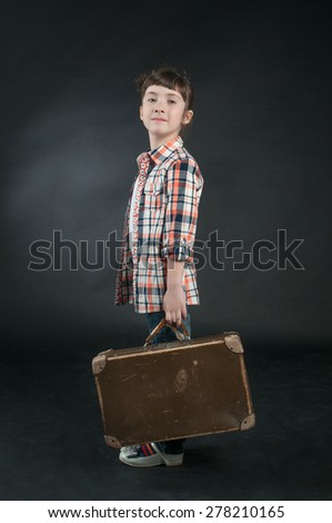 Adorable little girl with old suitcase - stock photo