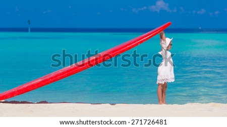 Adorable little girl with red big surfboard during tropical vacation