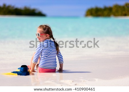Adorable little girl with snorkeling equipment at beach during summer vacation - stock photo