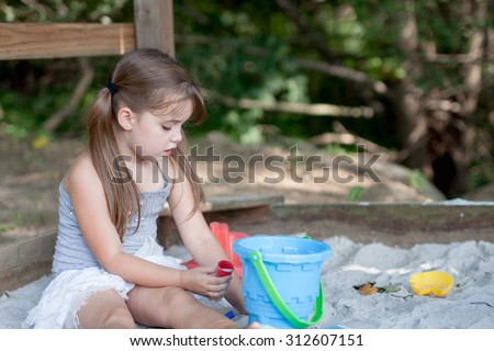 adorable little girl with two pig tails playing in sandbox in shaded area outside her home - stock photo