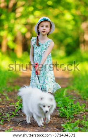Adorable little girl with white pomeranian spitz on path in park in summertime - stock photo
