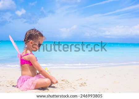 Adorable little girl with wings like butterfly on beach vacation - stock photo
