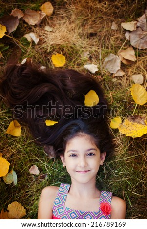 Adorable little girl with yellow leaves lies in yellow leaves - stock photo