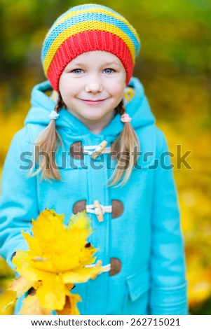 Adorable little girl with yellow maple leaves outdoors at beautiful autumn park - stock photo