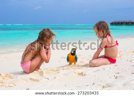 Adorable little girls at beach with colorful parrot - stock photo