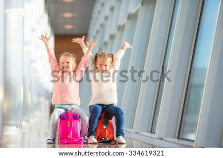 Adorable little girls having fun in airport sitting on suitcase waiting for boarding - stock photo