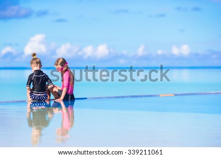Adorable little girls in outdoor swimming pool on summer vacation - stock photo