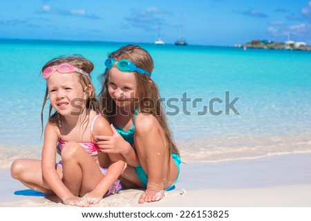 Adorable little girls in swimsuit and glasses for swimming at beach
