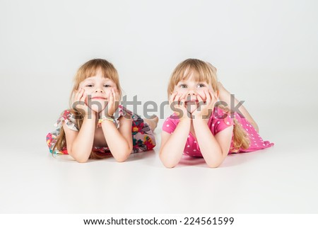 Adorable little girls laying on the floor and looking up on white background - stock photo