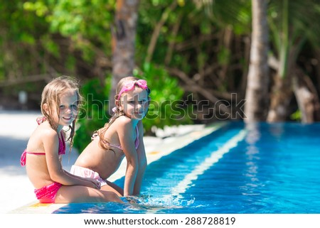 Adorable little girls playing in outdoor swimming pool - stock photo
