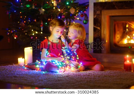 Adorable little girls playing with Christmas lights by a fireplace in dark and cozy dining room - stock photo