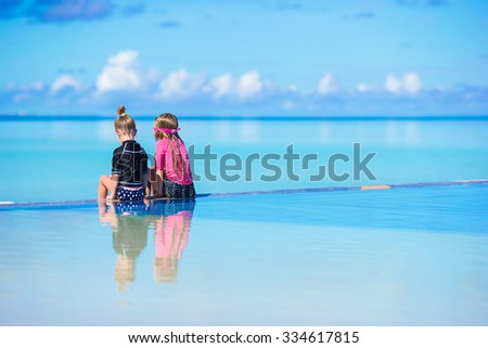 Adorable little girls relax in outdoor swimming pool on tropical vacation - stock photo